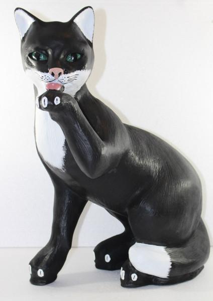 Dekofigur Katze sitzend Pfote am Mund schwarz weiß gefleckt H 48 cm Deko Katzenfigur aus Kunstharz